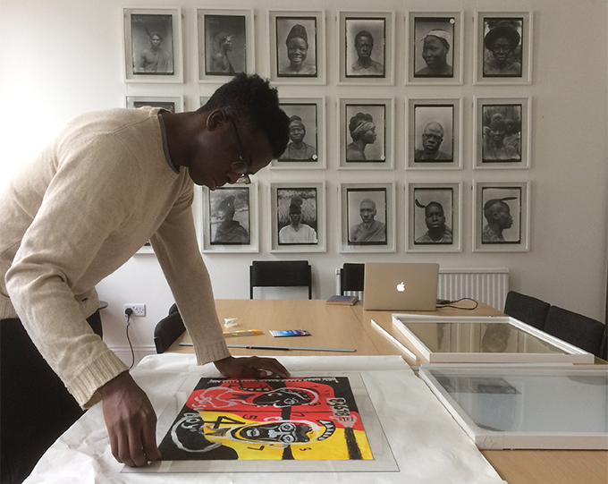 Chiadikobi Nwaubani installing 'Susu Boy' as part of the Photographic Affordances exhibition at the Royal Anthropological Institute, London.