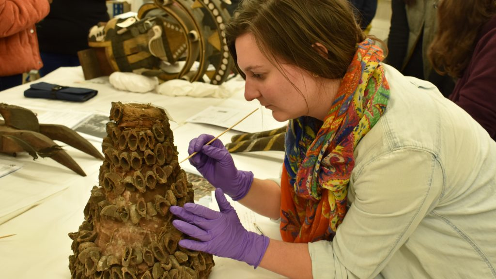 UCL Conservation student conducting visual inspect of headdress collected by N. W. Thomas for condition report