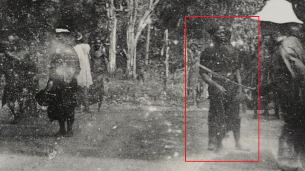 A police officer caught in the background of a panoramic photograph taken during Northcote Thomas's 1910-11 tour of Awka District