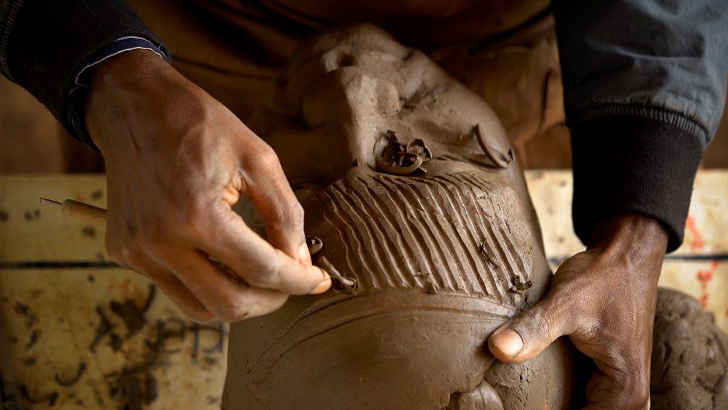 Ozioma Onuzulike in his studio inscribing ichi marks on face fragments
