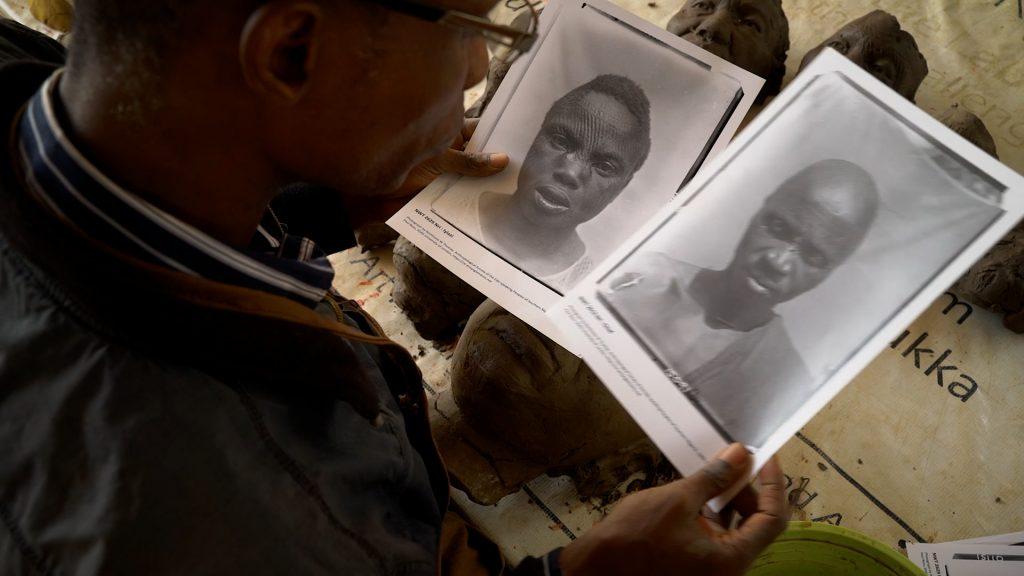 Ozioma Onuzulike in his studio looking at Northcote Thomas photographs of ichi marks