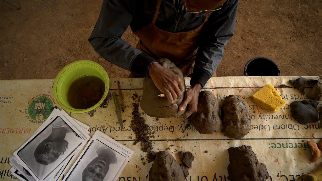 Ozioma Onuzulike in his studio making face fragments